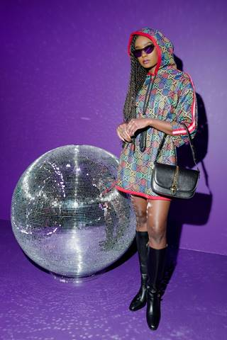 KiKi Layne wore a Gucci black and multicolor GG Psychedelic printed nylon hooded dress with pink and red stripes down the sleeves with black leather knee-high boots and a black leather Sylvie 1969 medium shoulder bag.